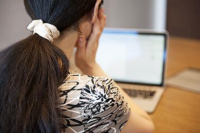 小林宏美さん(仮名)の後ろを向いてパソコンを見ている写真